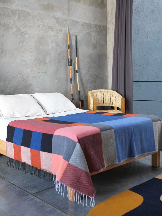 bed with colorful colorblocked blanket