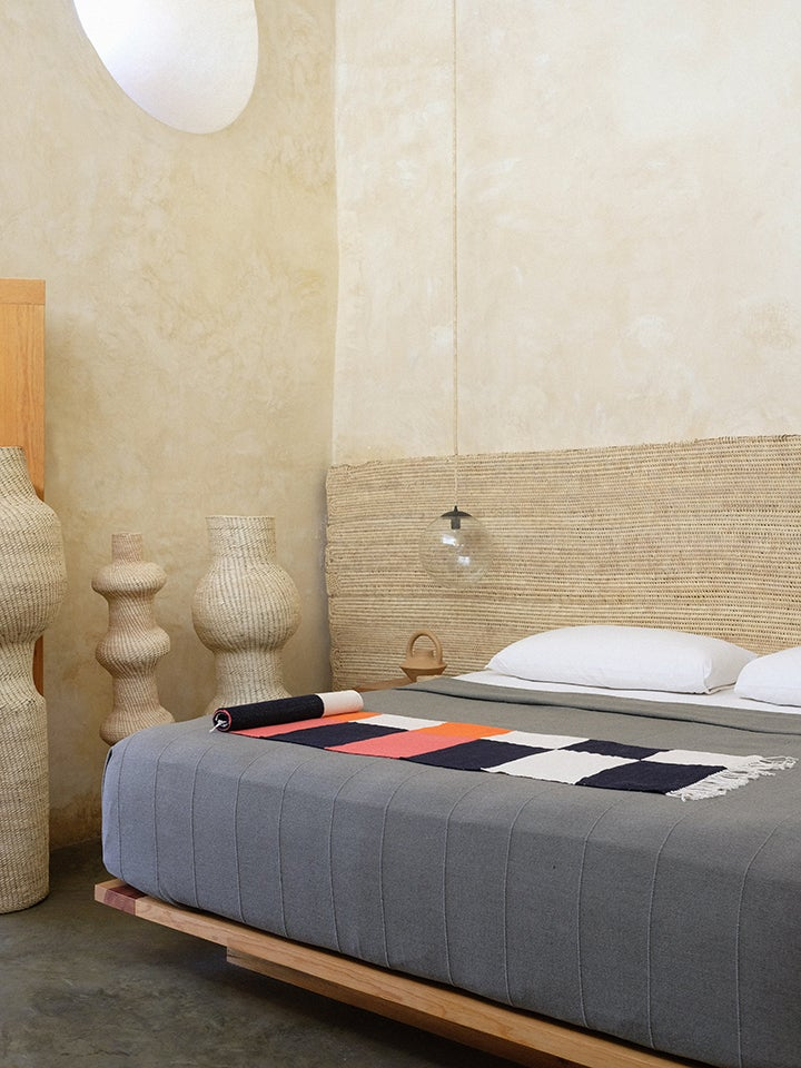 bed with raffia headboard and graphic bedspread