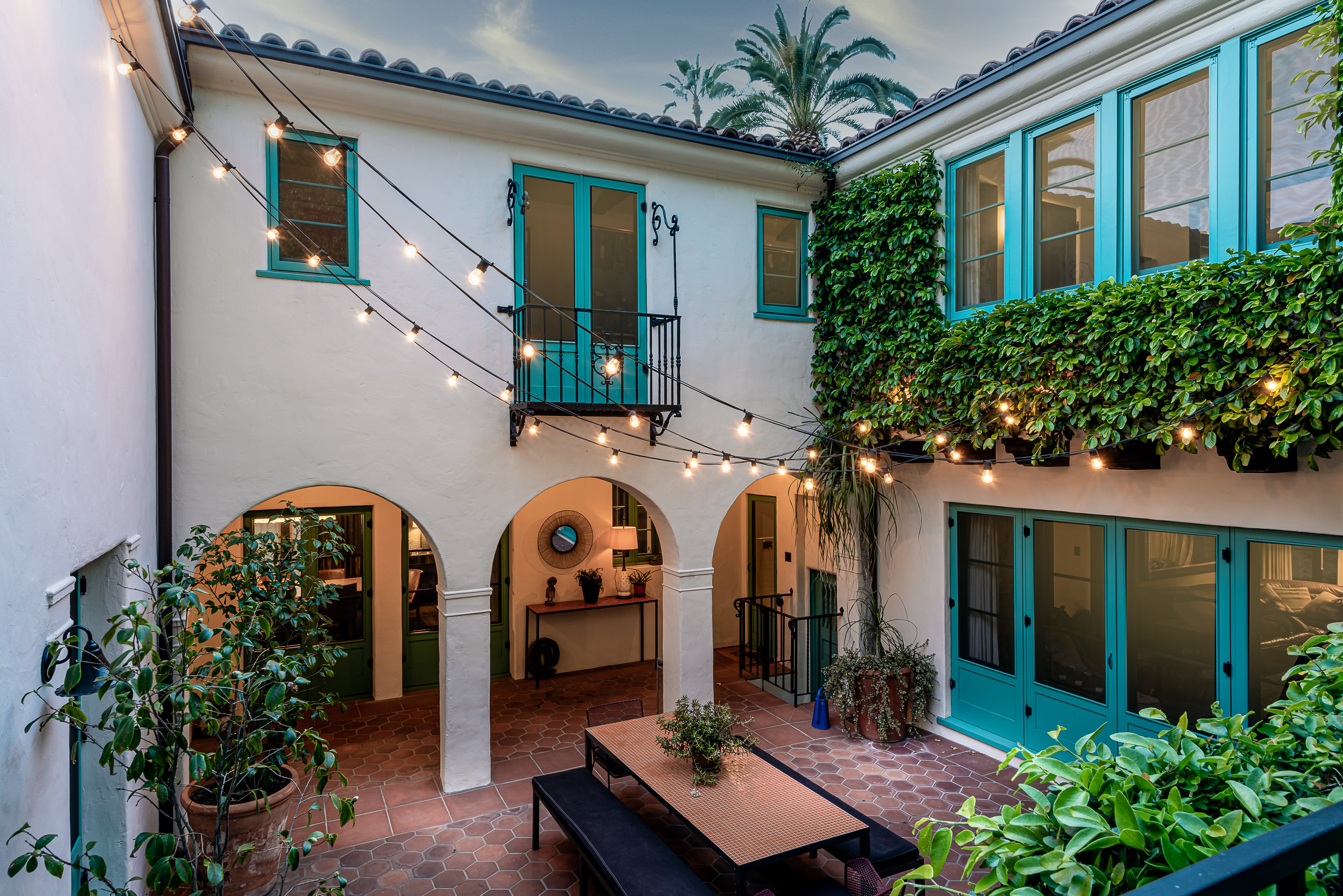 Courtyard of a Spanish Colonial-style home with aquamarine doors