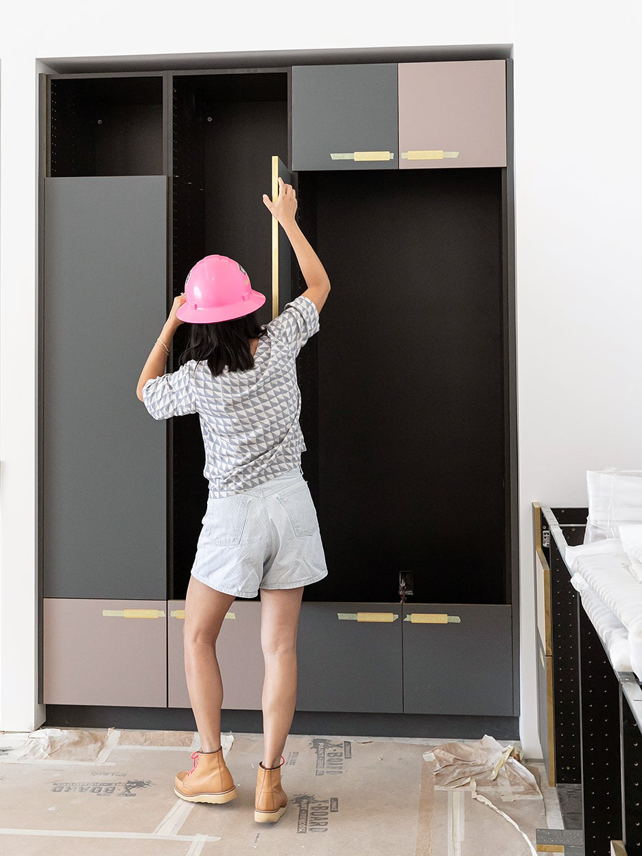 woman measuring cabinets