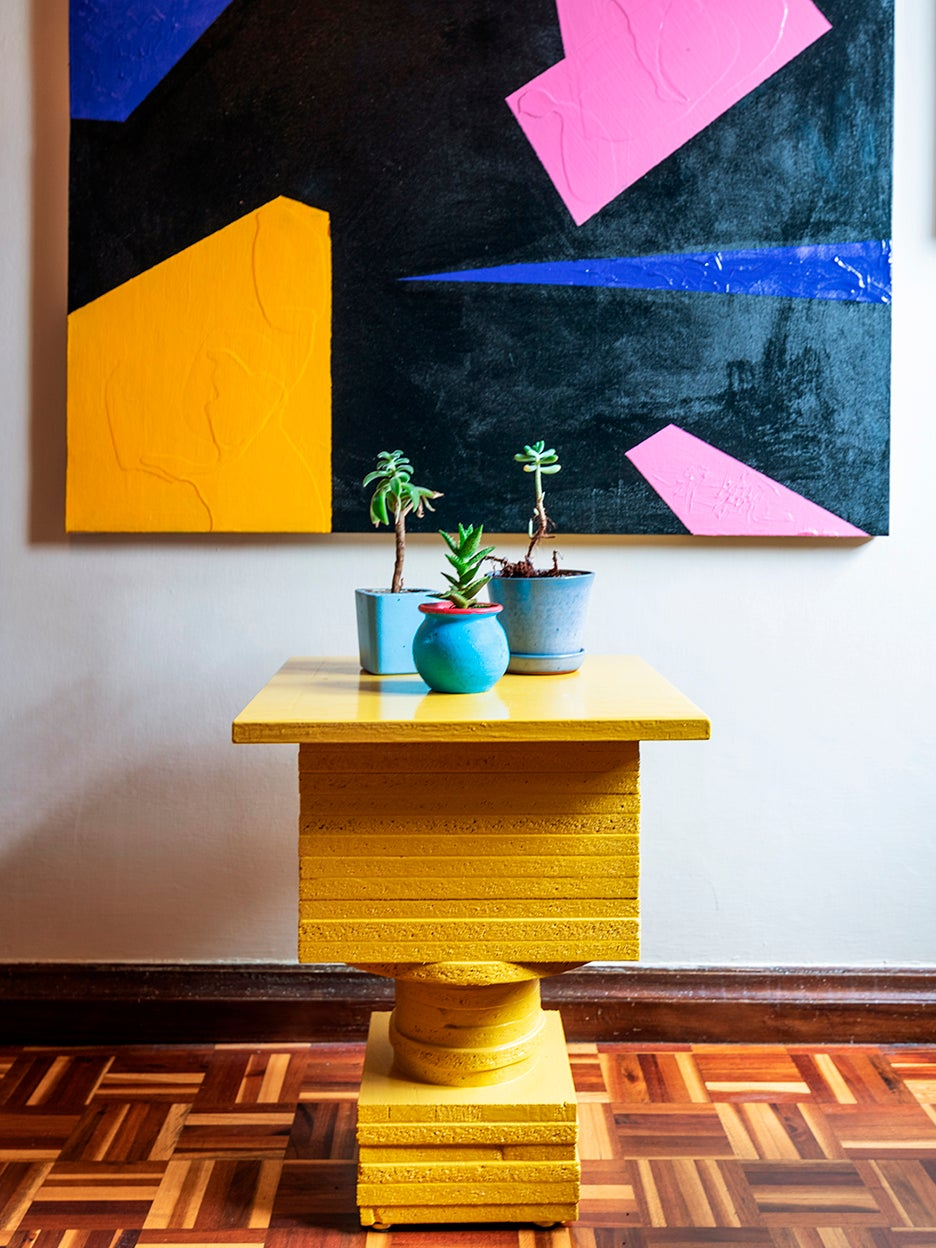 yellow side table below graphic artwork