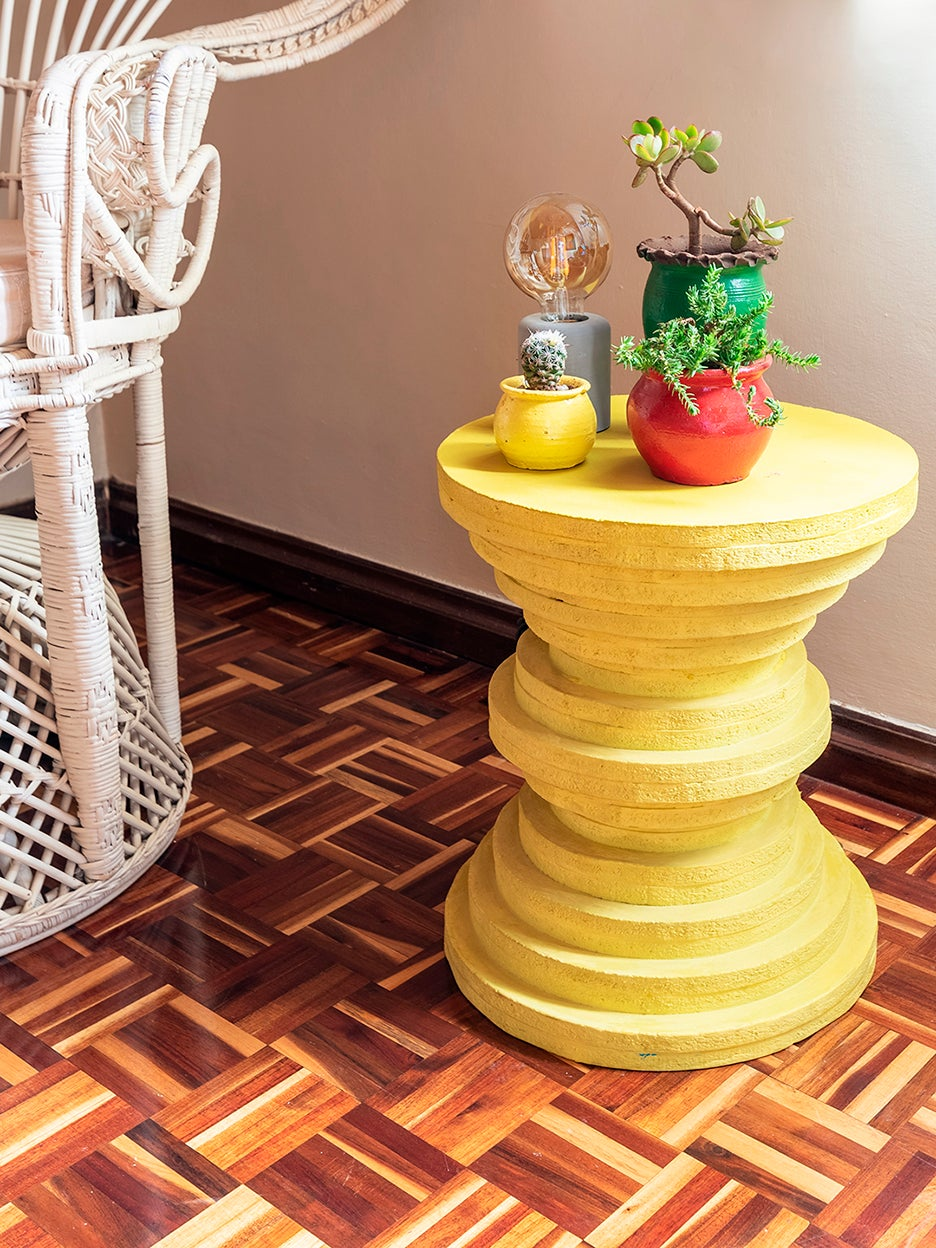 round yellow side table made of stacked discs