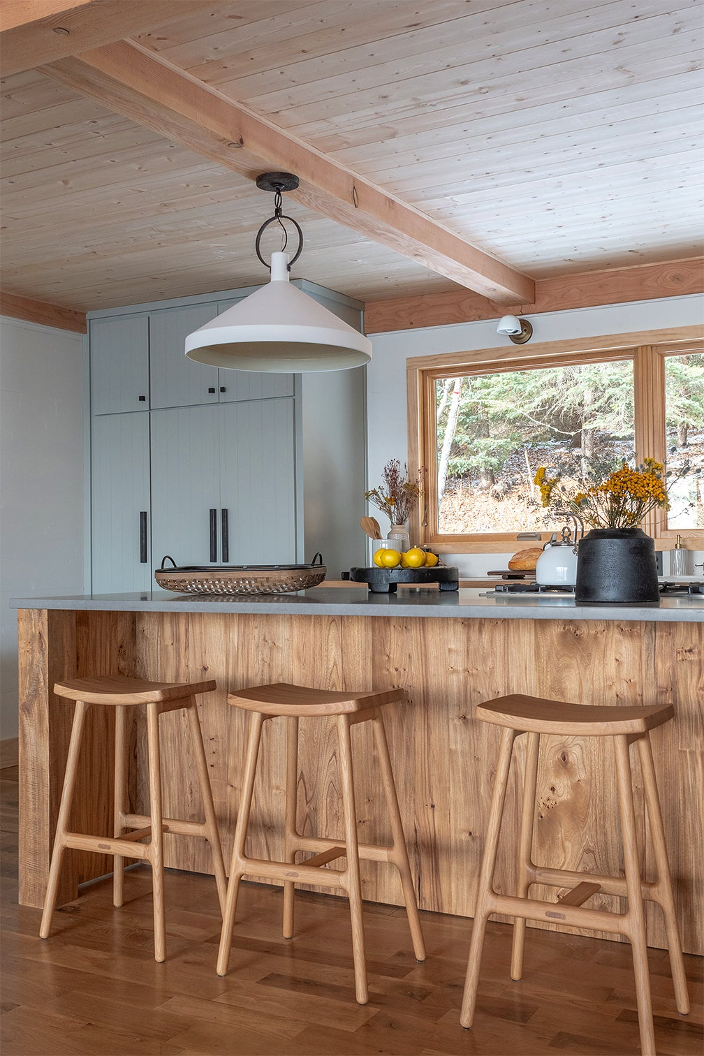wood kitchen island with pale blue cabinets