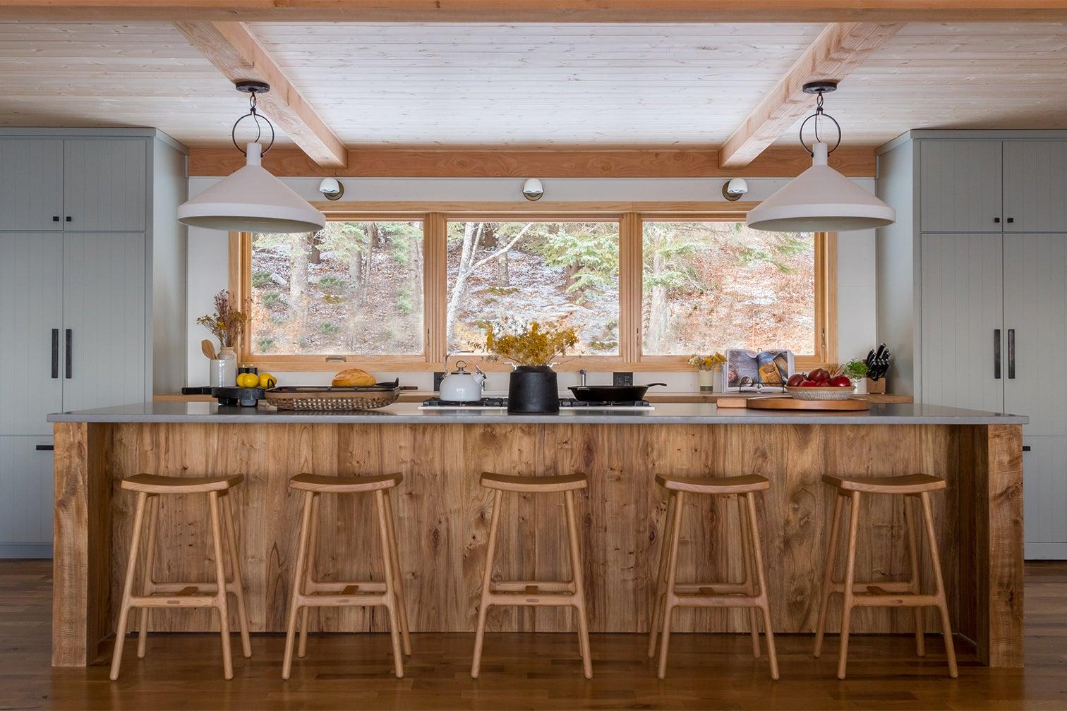 large kitchen island facing sink under big windows