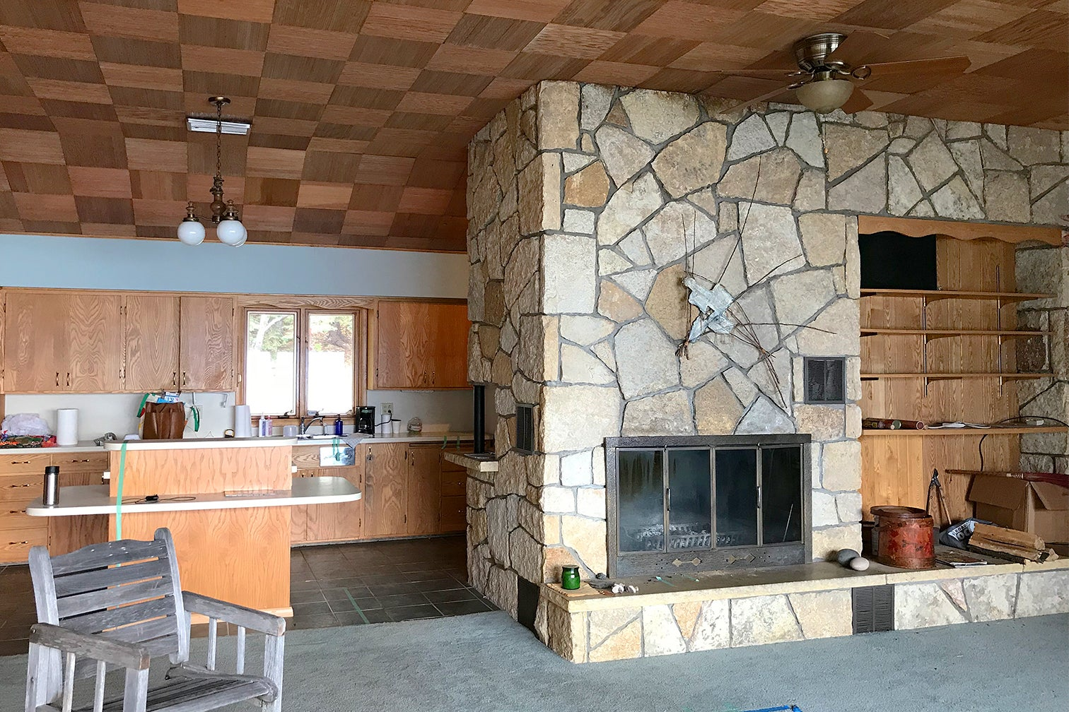 stone fireplace next to dated kitchen