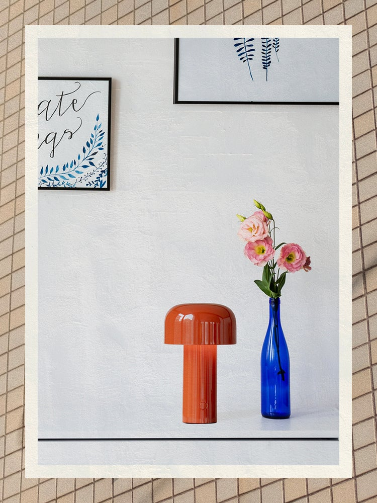 Red desk lamp next to a blue vase of flowers