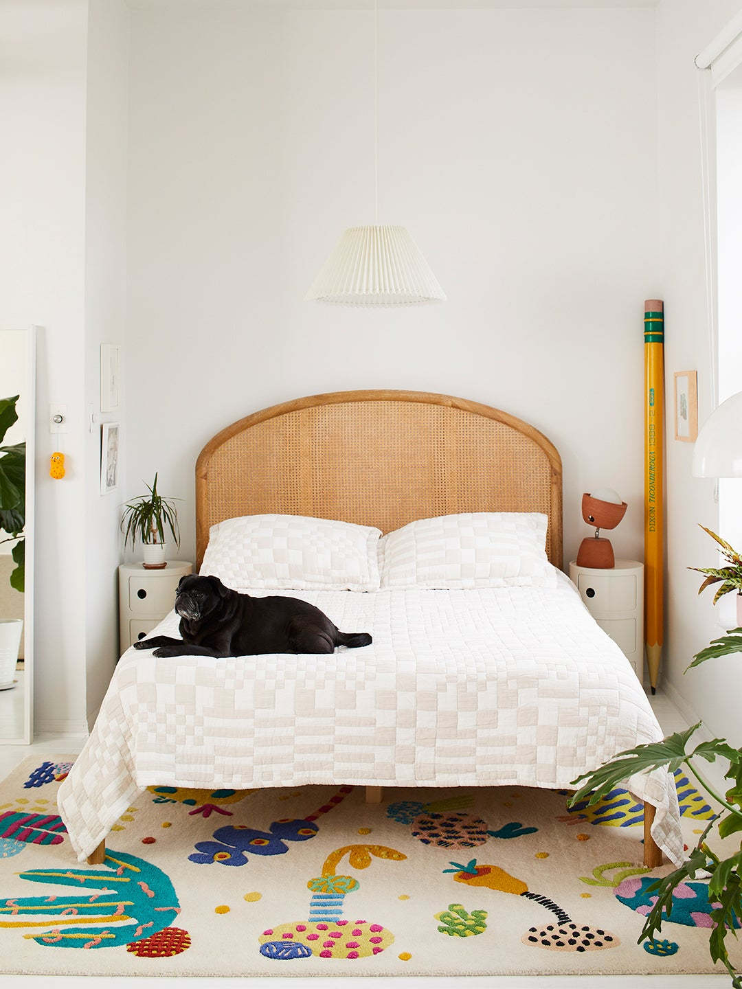 Bed with cane headboard and white bedding