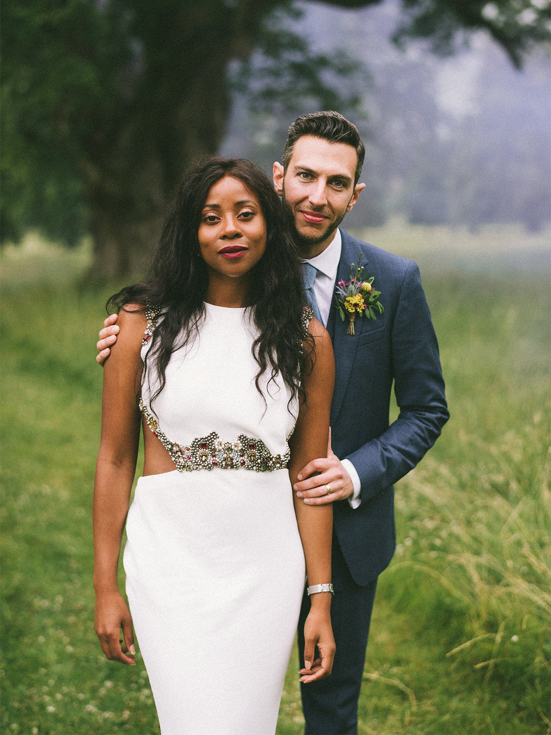 couple posing at their wedding in field