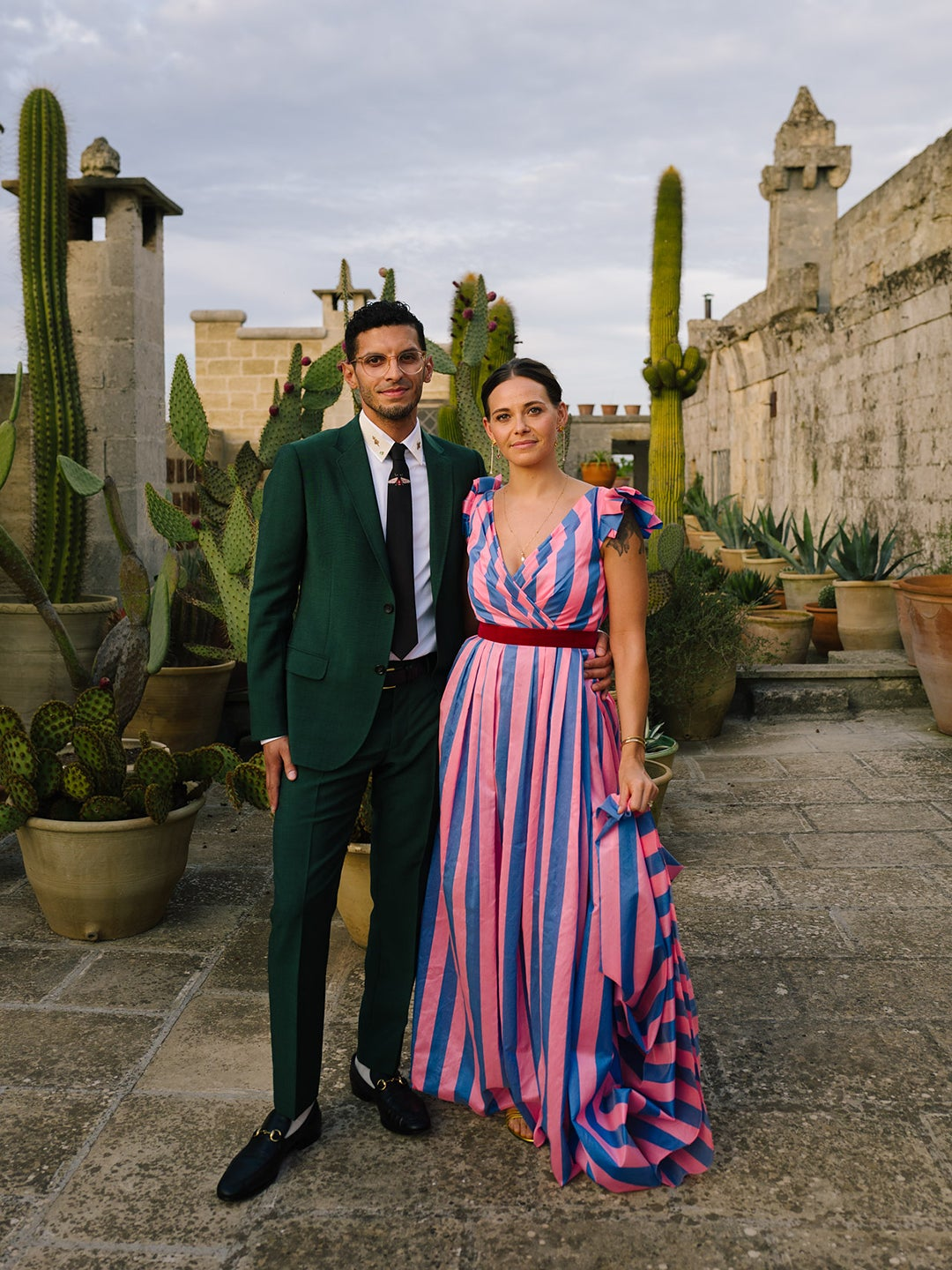 bride in pink and blue striped dress and groom in suit