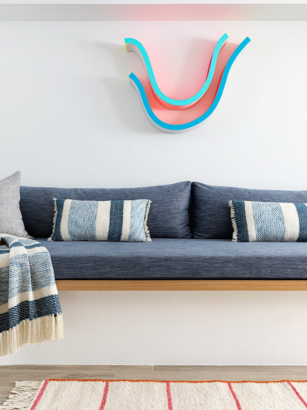 A Cool Wavy Sofa Actually Conceals Ductwork in This Family's Brownstone Basement
