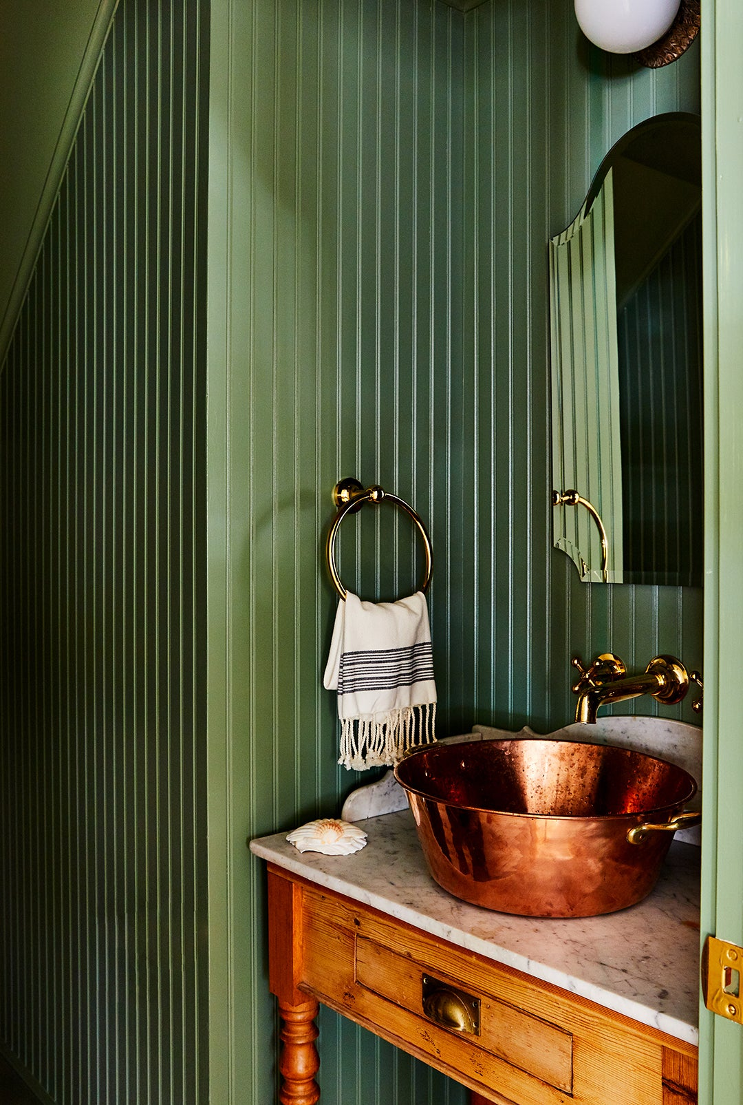 green paneled powder room with brass sink