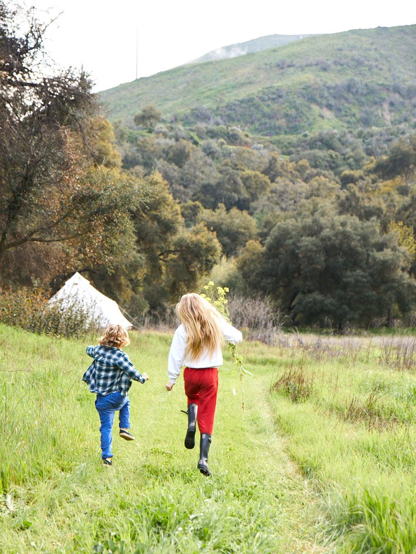 Two kids skipping in a field.