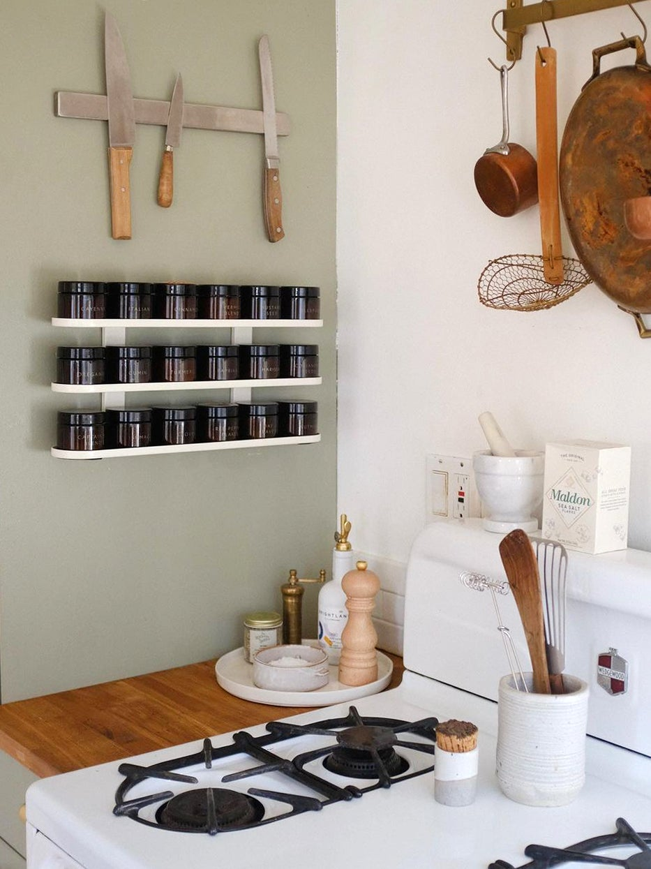 white spice rack on green kitchen wall