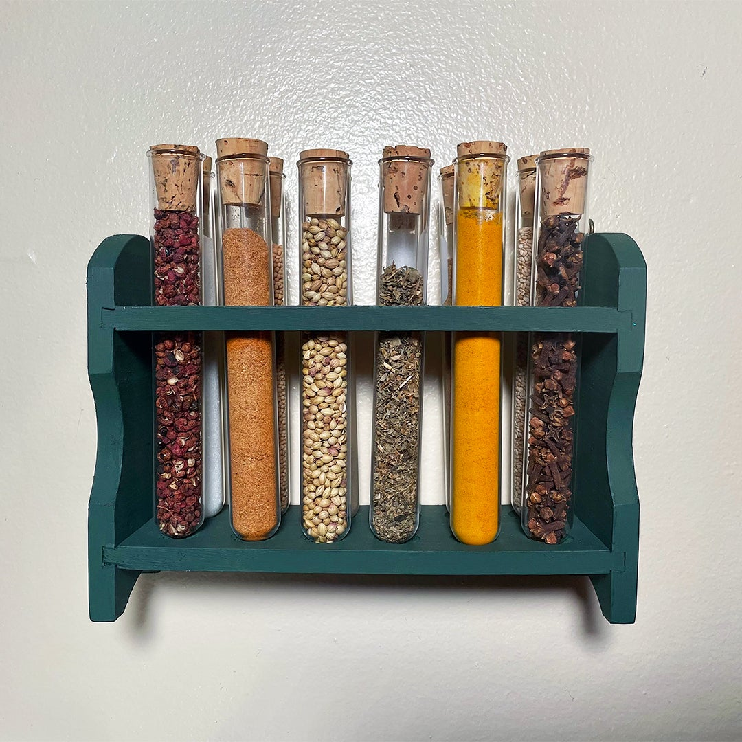 spices in test tubes in green wall rack