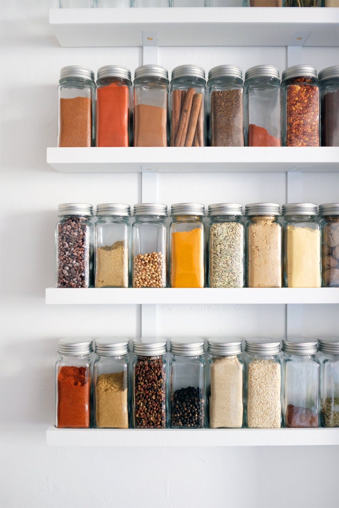jars of spices on white shelves