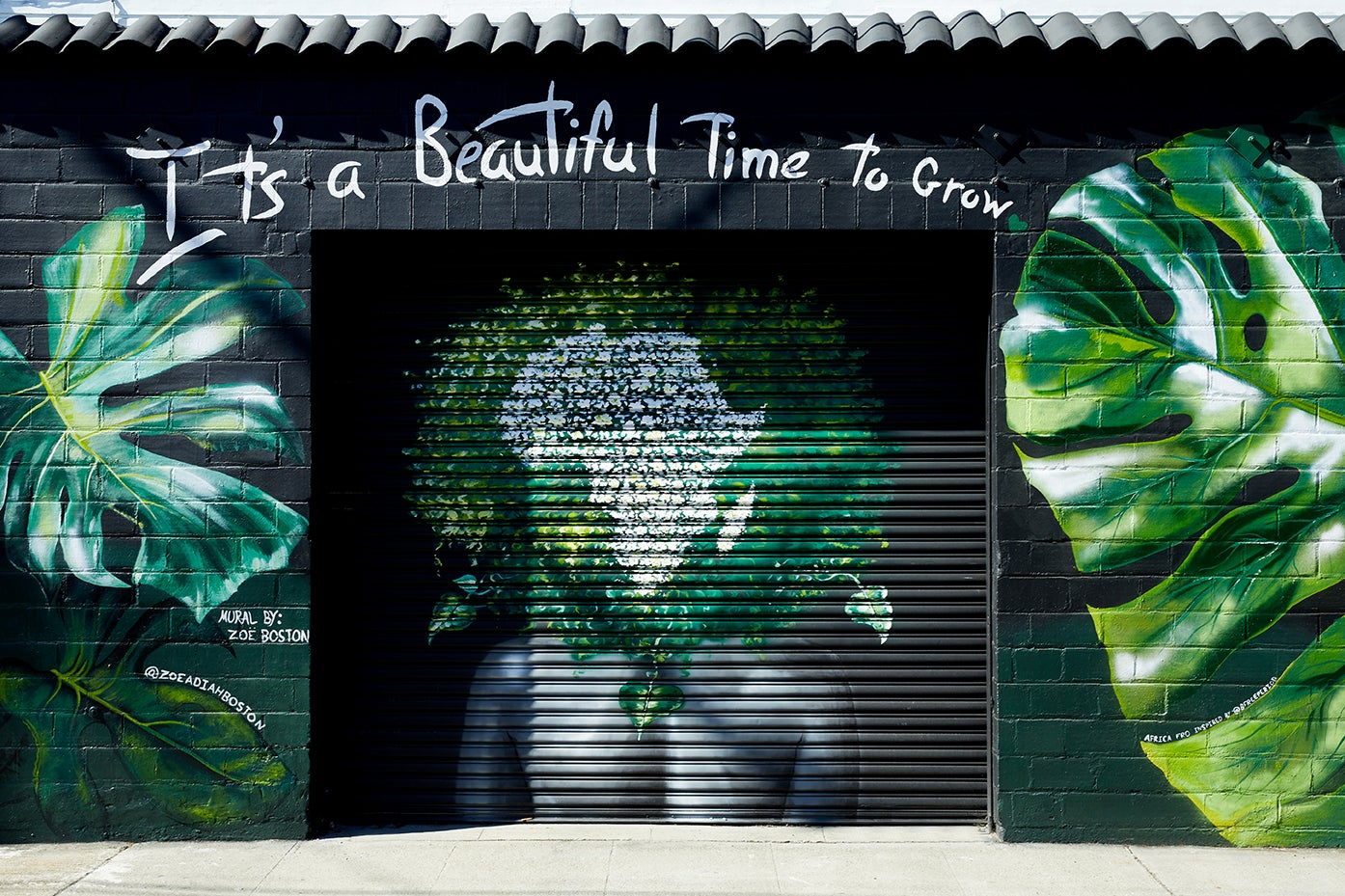 black garage with plant mural