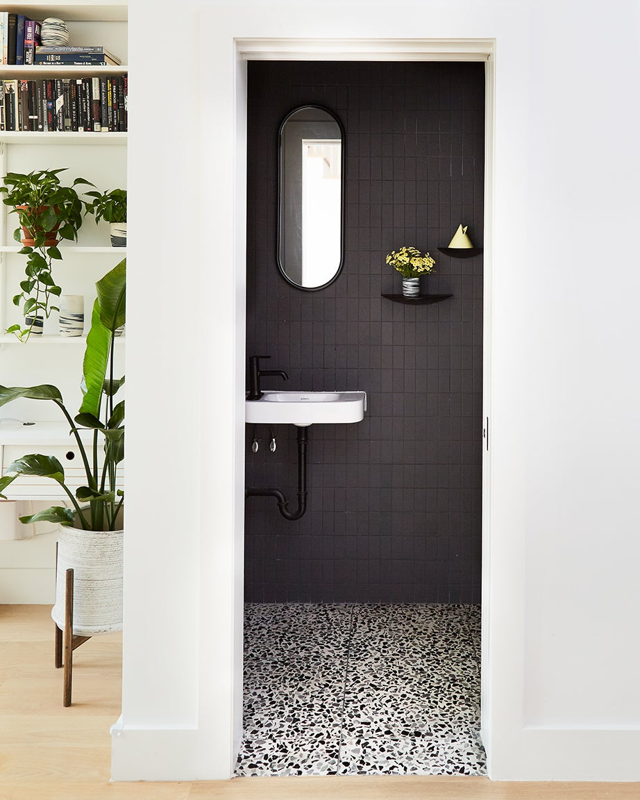 Black wall tiles, white sink and black mirror