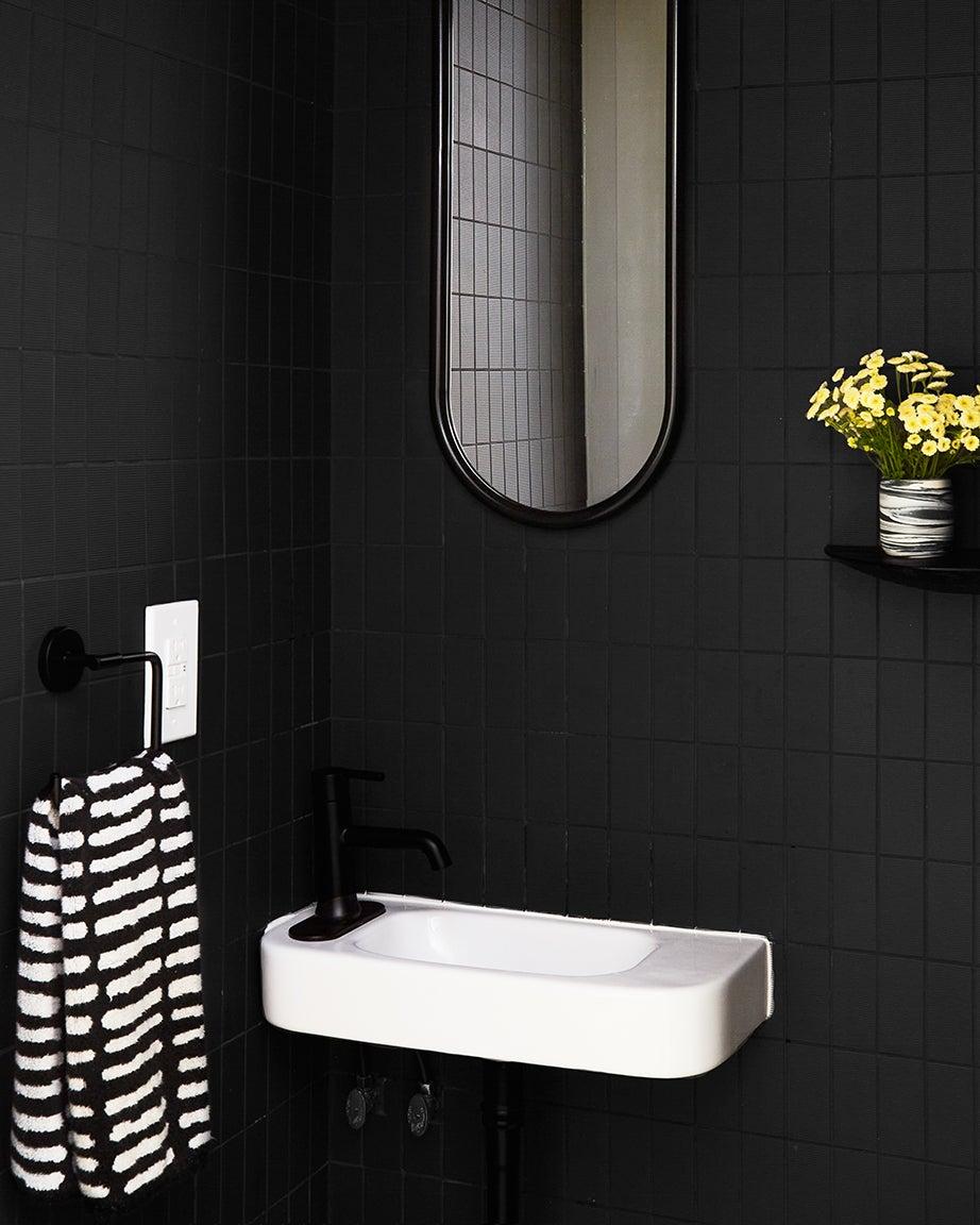 Black tiles, white sink and black mirror