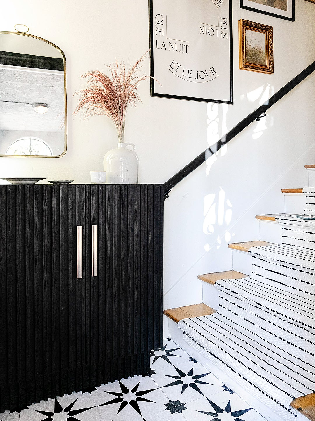 Entryway, Dowel IKEA cabinet, painted black, stair runner, and gallery wall