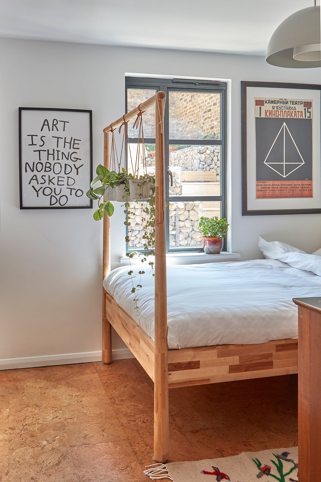 four poster bed with plants hanging from it