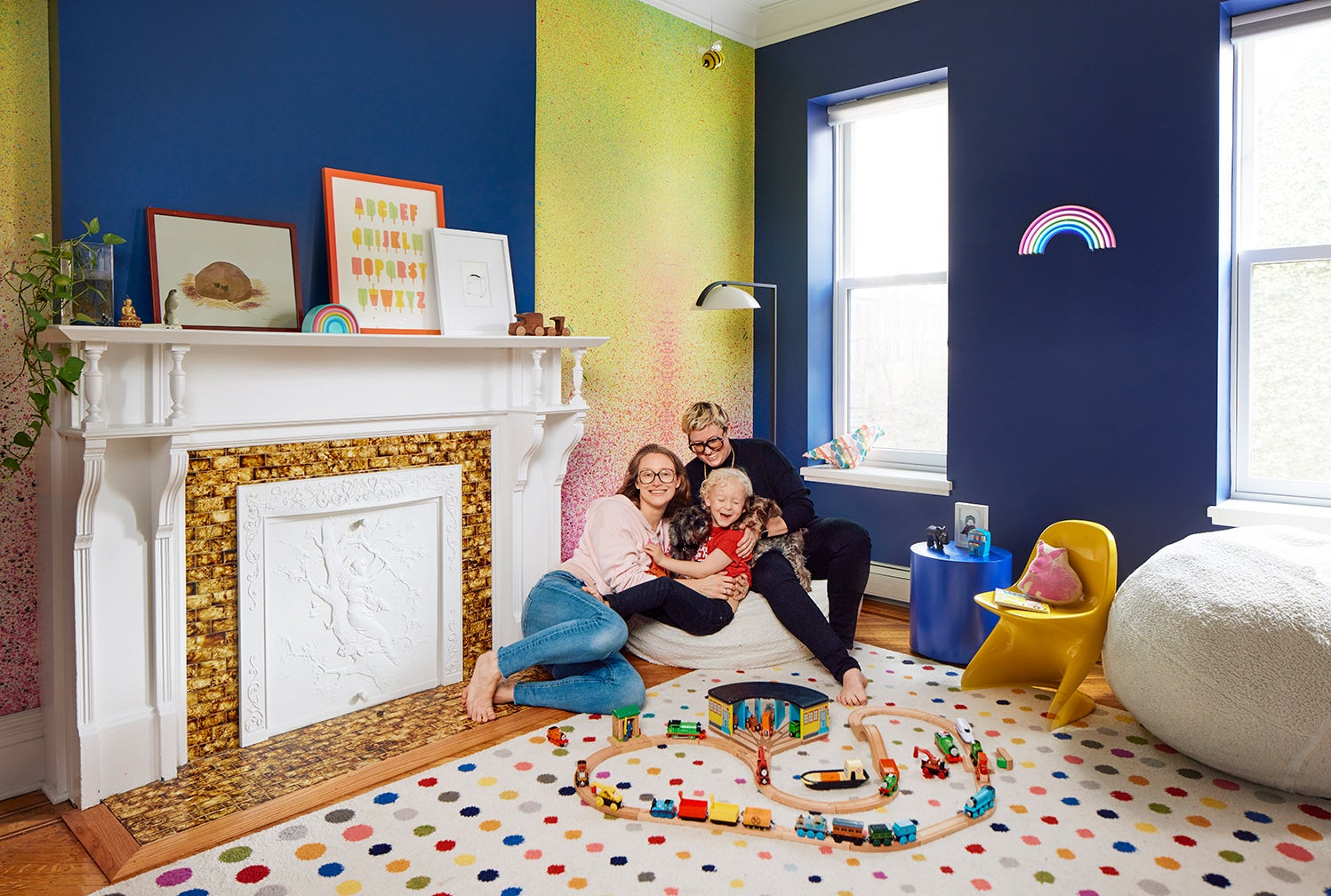 Family of three lounging on bean bag at home in Brooklyn.