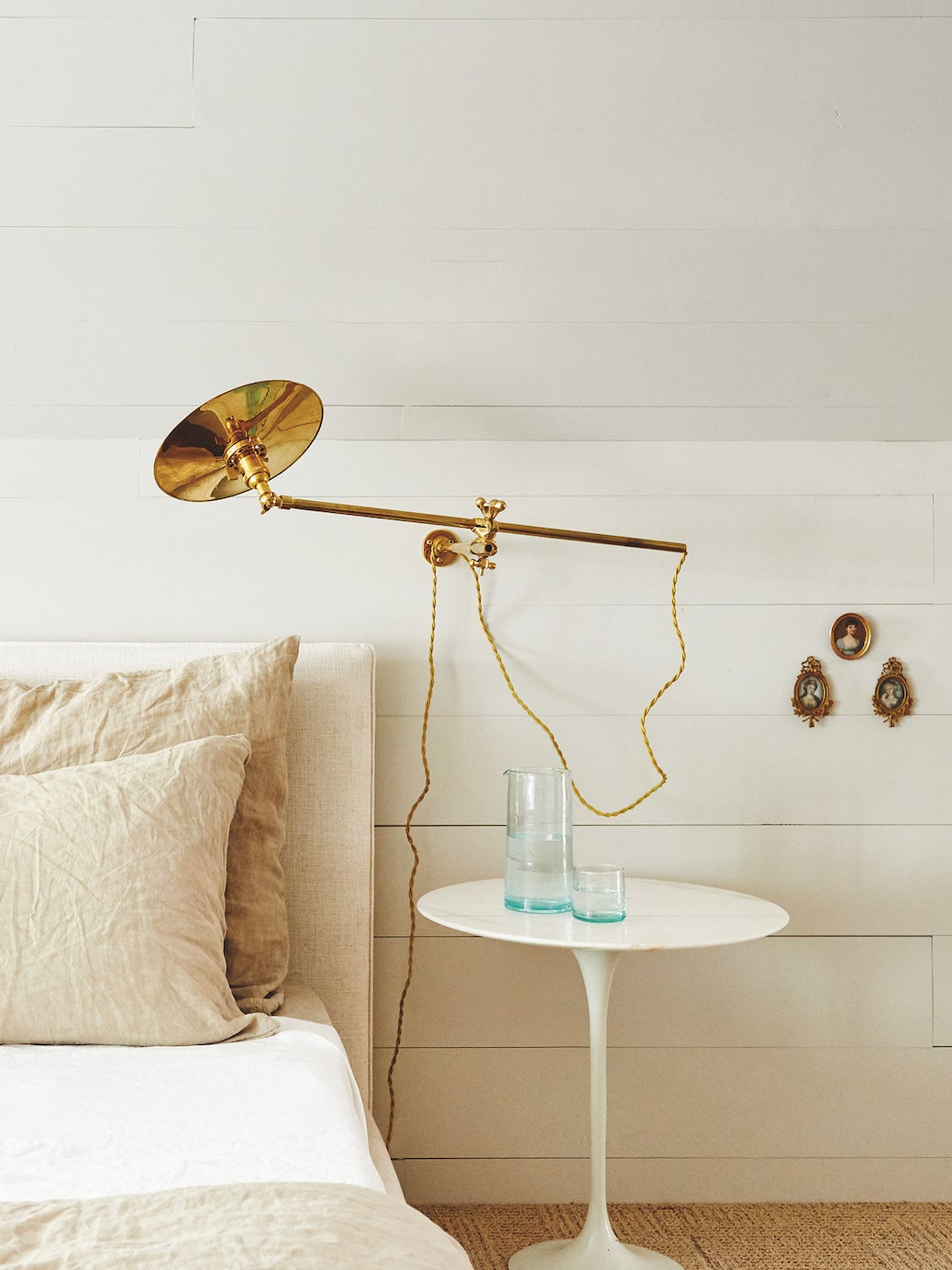 neutral bedroom with gold sconce