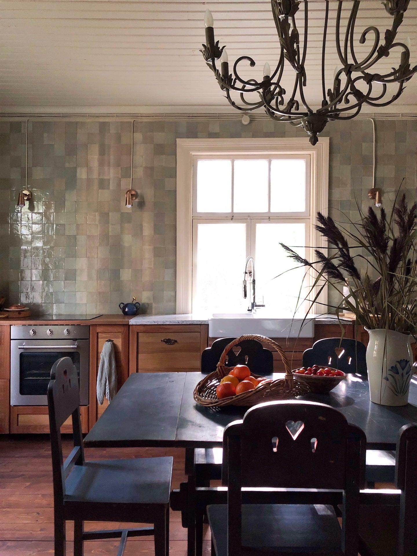 green tiled wall with black dining table