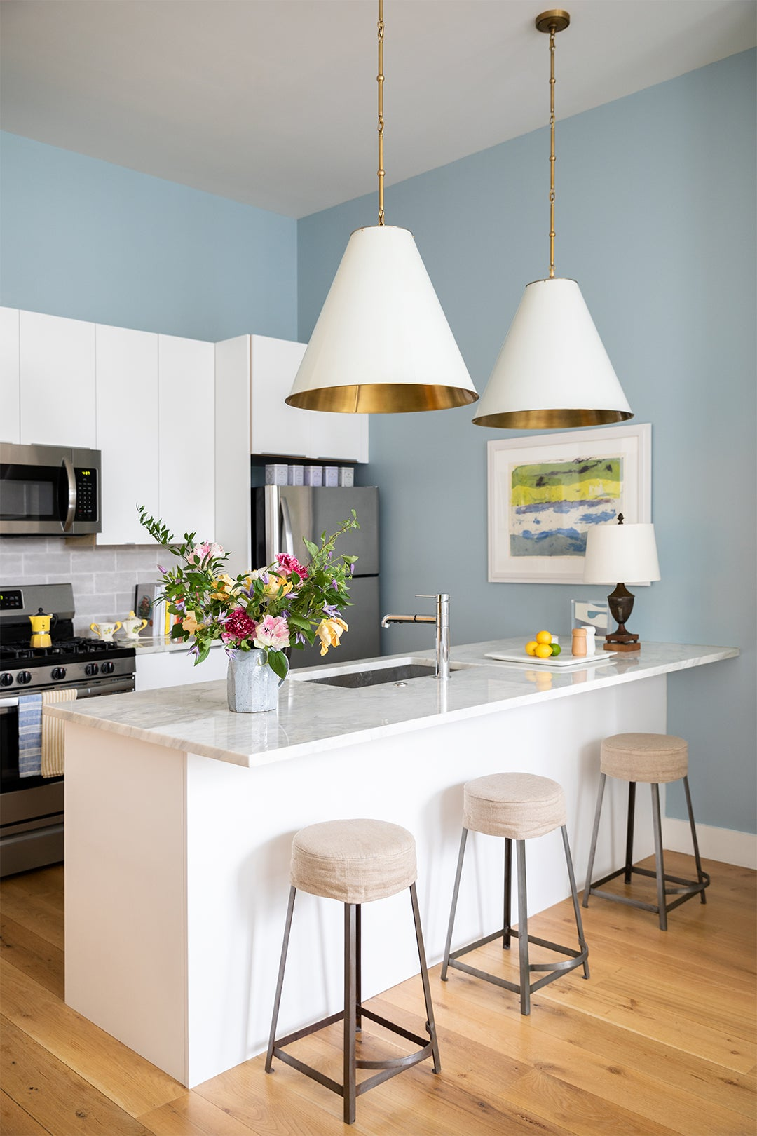 Painted Kitchen Island With Three Bar Stools and Large Pendant Lights