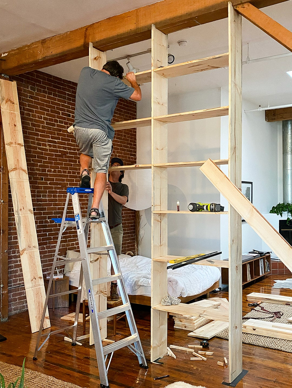 man leveling shelves