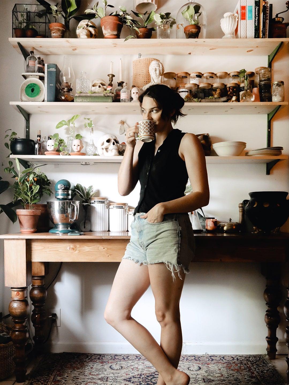 Brooke Darwin Drinking Coffee in Dark Kitchen