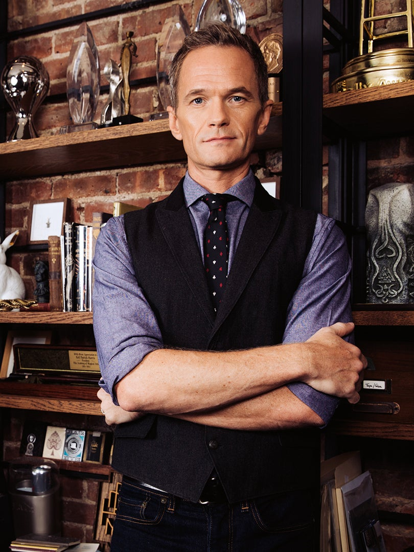 Neil Patrick Harris stands in front of bookcase
