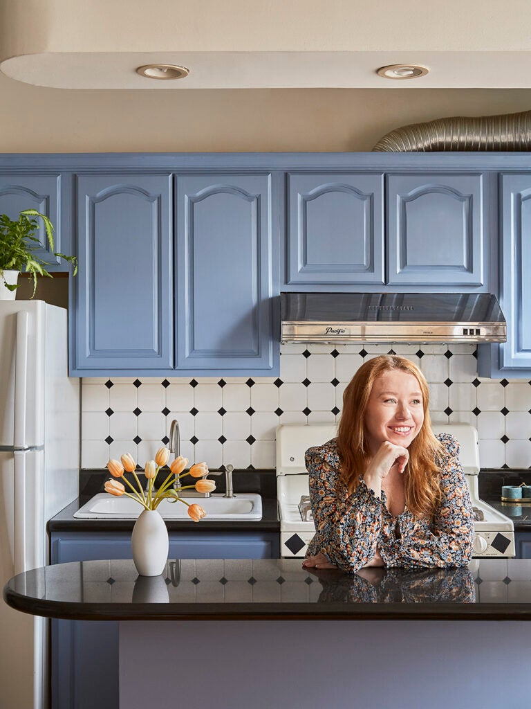 portrait of girl in a kitchen with blue cabinets