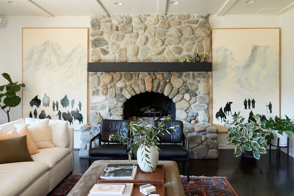 living room with fireplace and artwork on either side.