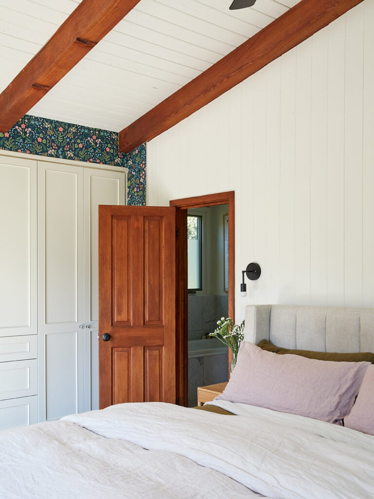 primary bedroom with beige sheets and navy wallpaper.