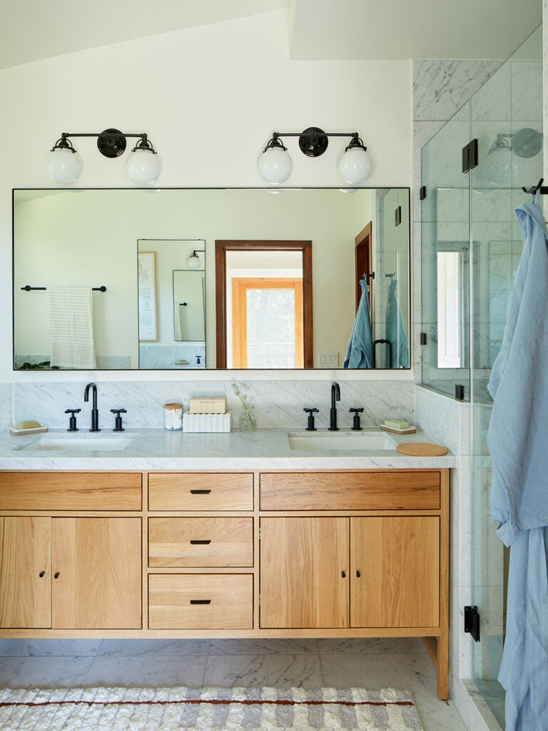 bathroom with wood vanity and marble counters.