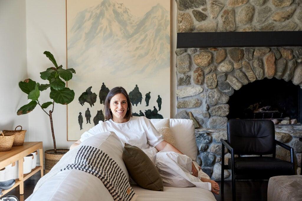portrait of michelle toney sitting on a white sofa.