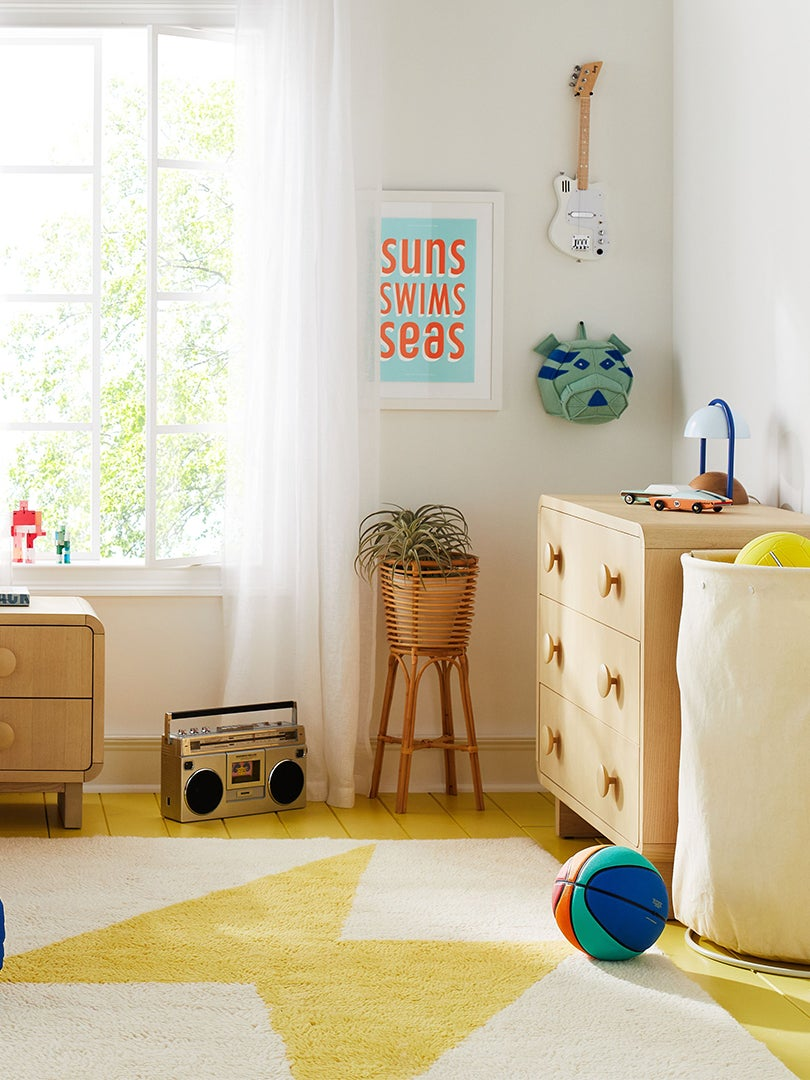 colorful kids bedroom with blue quilt and yellow rug