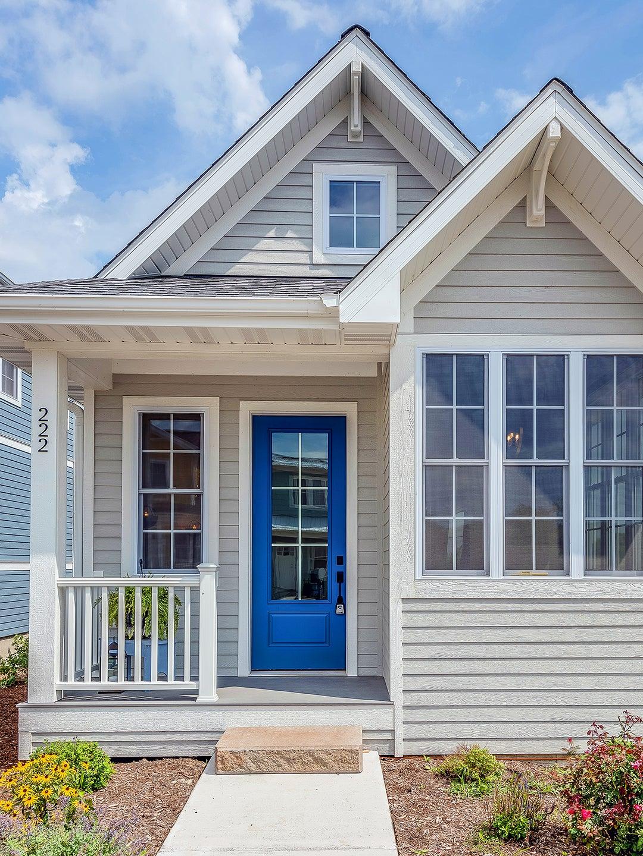grey home exterior with blue door